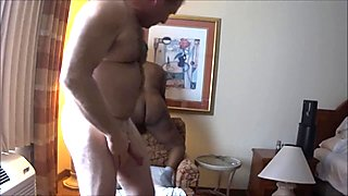 Interracial Couple Hotel Love Making In a Chair Angle Two
